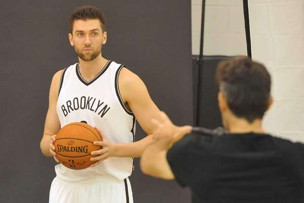 Brooklyn Nets' Andrea Bargnani listens to a photographer
