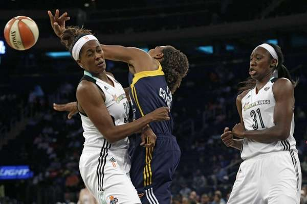 Indiana Fever forward Tamika Catchings, center, passes the