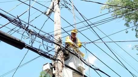 A PSEG Long Island utility worker works on
