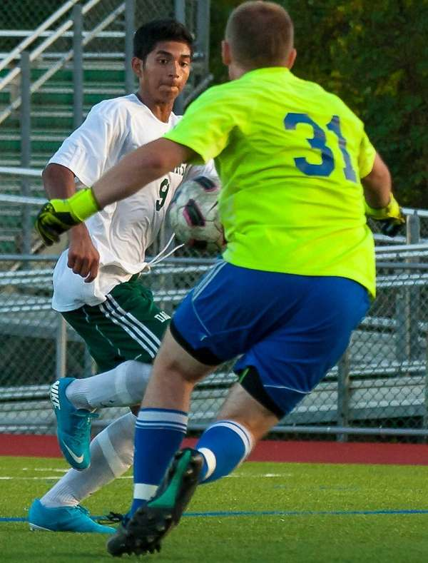 Farmingdale's Louis Zuniga, left, dribbles the ball on