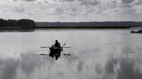 A man returns to shore in his kayak