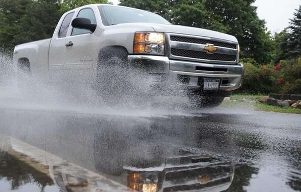 A vehicle plows through a large puddle on