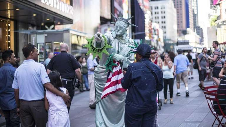 Costumed characters work the crowd in Times Square