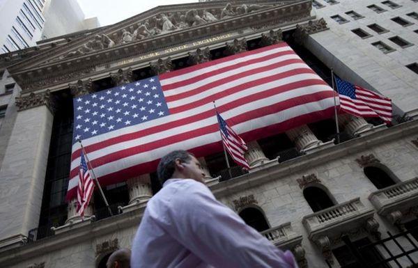 A pedestrian walks past the New York Stock
