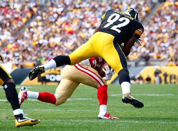James Harrison of the Pittsburgh Steelers tackles Carlos