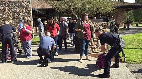 Police search students outside Umpqua Community College in