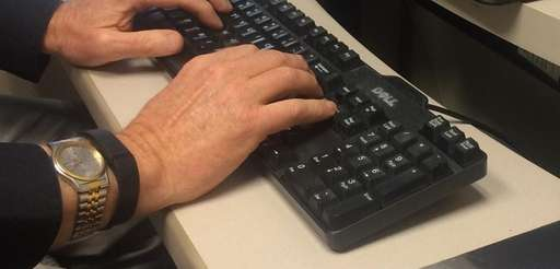 Michael Dobie typing on his computer with his