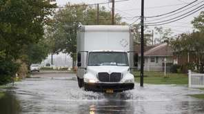 A truck passes through minor street flooding near