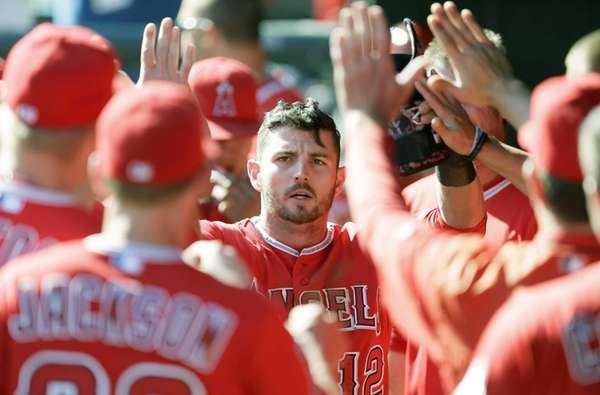 Los Angeles Angels' Johnny Giavotella is congratulated in