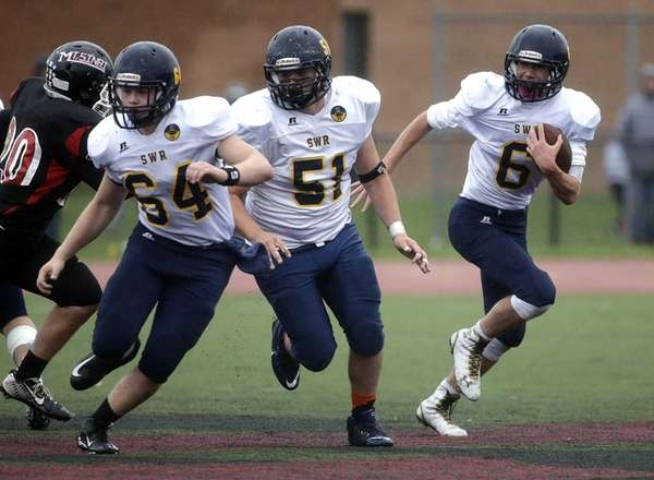 Shoreham-Wading River quarterback Jason Curran (6) runs around