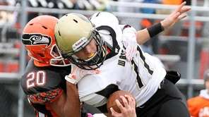 Wantagh's Dylan Beckwith gets tackled by Carey's Angelo