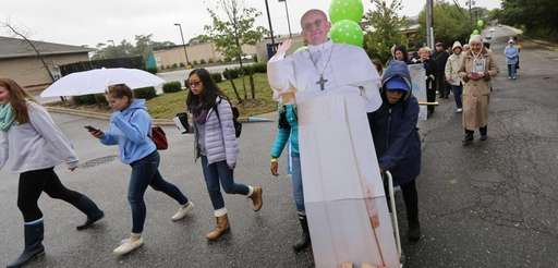 A cardboard cutout of Pope Francis is pushed
