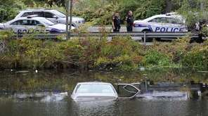 A car sits partially submerged in water after