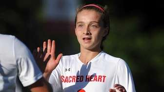Sacred Heart's Caitlin Kennedy, right, gets congratulated by