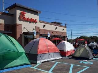 People set up tents in the parking lot
