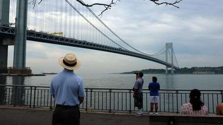 A man looks out at the Verrazano Bridge