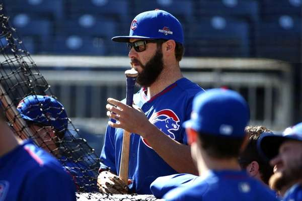 Chicago Cubs starting pitcher Jake Arrieta, center, stands