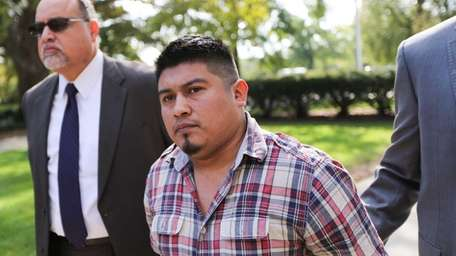 Wuilmer Mendosa, 32, is led into Nassau County