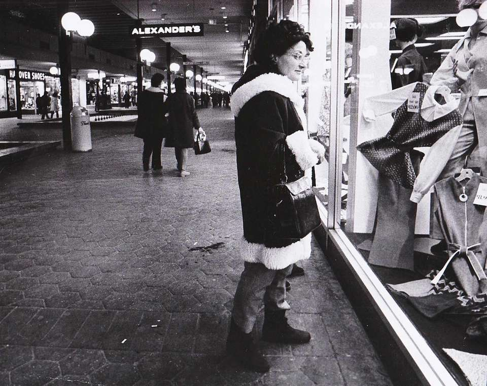 A shopper pauses at a display window in