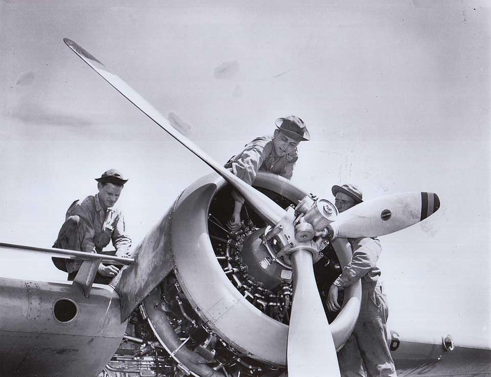 Three mechanics work on a plane in 1942