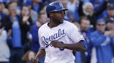 Kansas City Royals' Lorenzo Cain, left, scores on