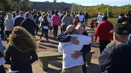 John Brower, 59, receives a hug from a