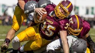 Kings Park's Jac Cutillo braves a tackle by