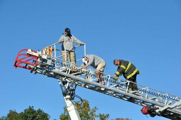 Firefighter Matt Stio assists Coach Tim Kopiske, left,