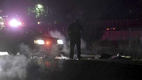 A Suffolk County police officer looks over debris