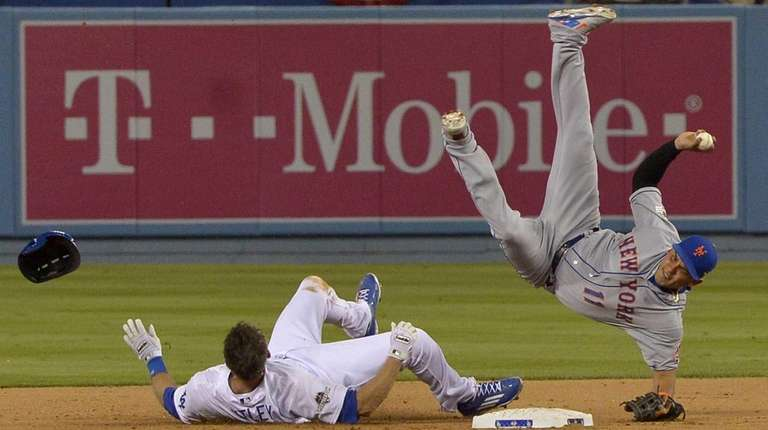 New York Mets shortstop Ruben Tejada falls after