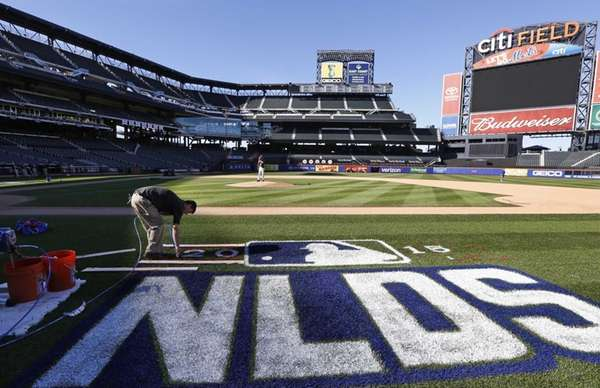 A worker paints the National League Division Series