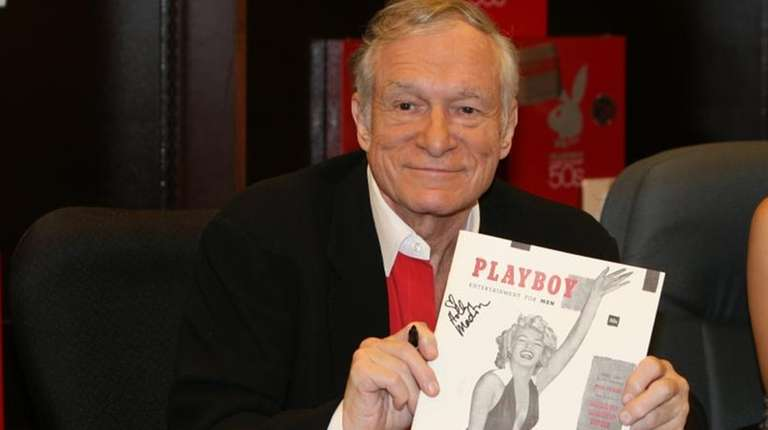 Hugh Hefner smiles while signing copies of the