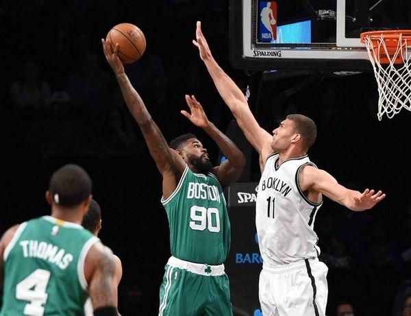 Boston Celtics forward Amir Johnson shoots and scores