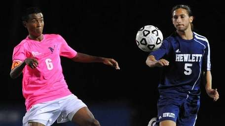 Manhasset's Kyle Peter, left, gets pressured by Hewlett's