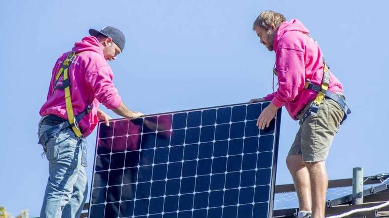 Employees of SUNation install solar panels at a