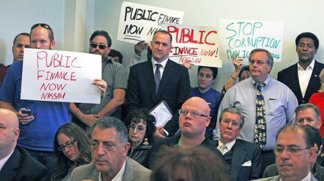 Members of the public listen as Kevan Abrahams,