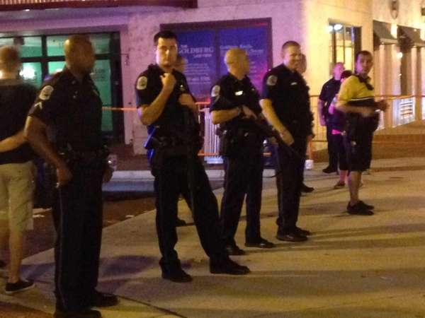 Police stand early Sunday, Oct. 18, 2015, near