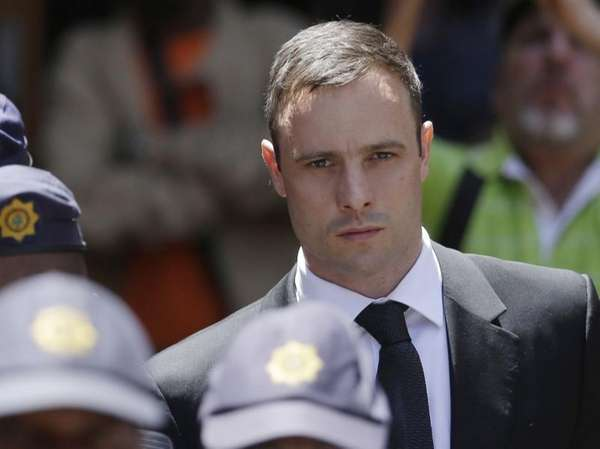 Oscar Pistorius is escorted by police officers as