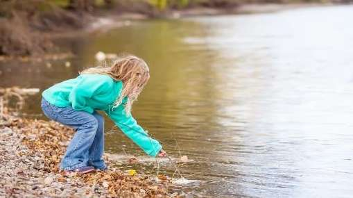 A girl in fleece playing on a river.
