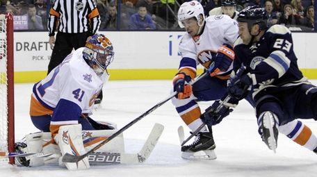 New York Islanders' Jaroslav Halak, left, makes a