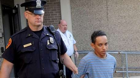 Orlen Soliz-Galvez, 18, of Amityville, is escorted out