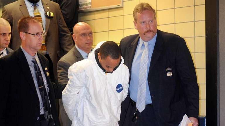 Tyrone Howard is escorted from the 25th Precinct