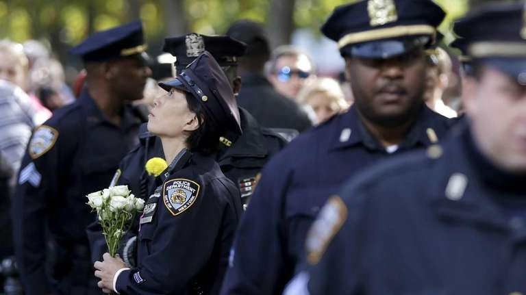 A police officer pauses before laying flowers in
