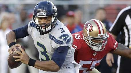 Seattle Seahawks quarterback Russell Wilson (3) scrambles away