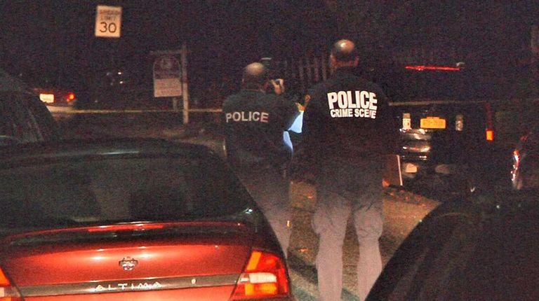 Police investigate the scene where a street robbery