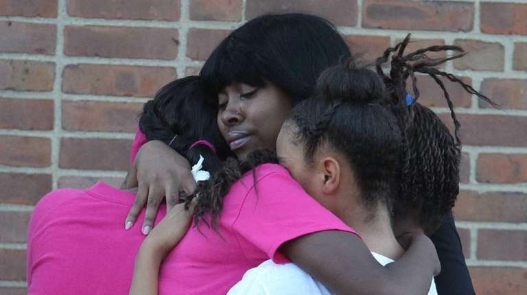 Mourners console each other on Friday, Oct. 23,