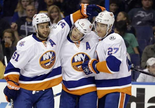 New York Islanders' Kyle Okposo, center, is congratulated
