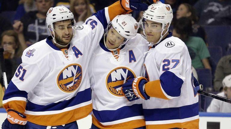New York Islanders' Kyle Okposo, center, is congratulated