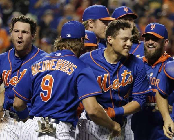 New York Mets' Wilmer Flores, center right, is