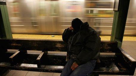 A homeless man sleeps as a Q train